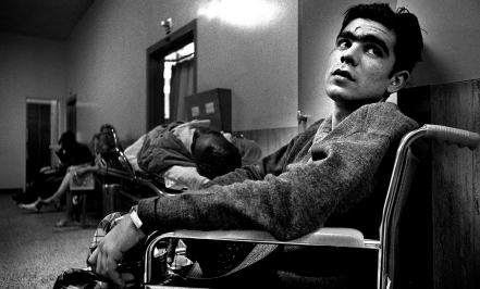 """The Drifter at San Francisco General Hospital. He woke up asking for his buddy who went out to get some cigarettes. He smoked a lot but I never saw him drink alcohol in public. The hospital was busy so our """"waiting room"""" was in the hallway next to a guy on a gurney."""