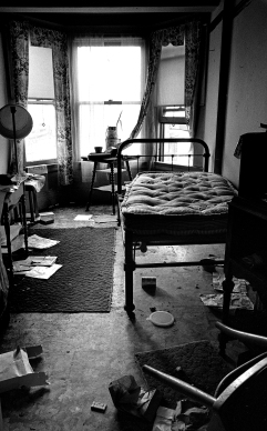 This was not an abandoned room. The guy living here said the hotel did not furnish anything except the room as is. The trash is the accumulation from previous tenants. He had been living here for a few days and will stay until his monthly pension runs out. Most of his pension was spent on liquor and food. Occasionally, he would be mugged when drunk on the streets. He slept on the streets until his next pension check arrived or sought shelter at the Salvation Army Harbor Light facility on 4th and Howard Streets. It depended on the weather.
