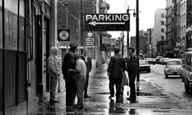 Police waiting for the paddy wagon as they round up the homeless on Skid Row. Often, the round up was initiated by storeowners who objected to them loitering outside their stores. During the cold rainy season, they homeless were happy with going to jail.