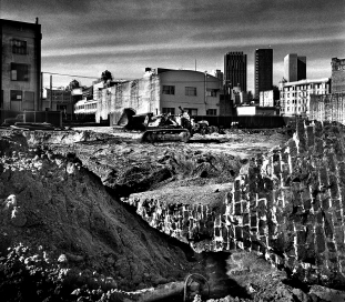 In 1966, the City of San Francisco approved plans for the Yerba Buena project to redevelop the area known as Skid Row. This project was interrupted by lawsuits in the 1970s as community leaders argued against the displacement of cheap housing. In 1970, the area was mainly dilapidated hotels, industrial buildings and open space parking lots.